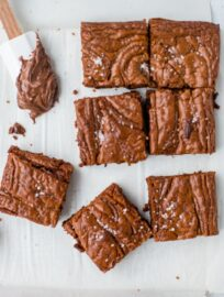 Close-up image of sea salt Nutella brownies with a small spatula dipped in the chocolate hazelnut spread.