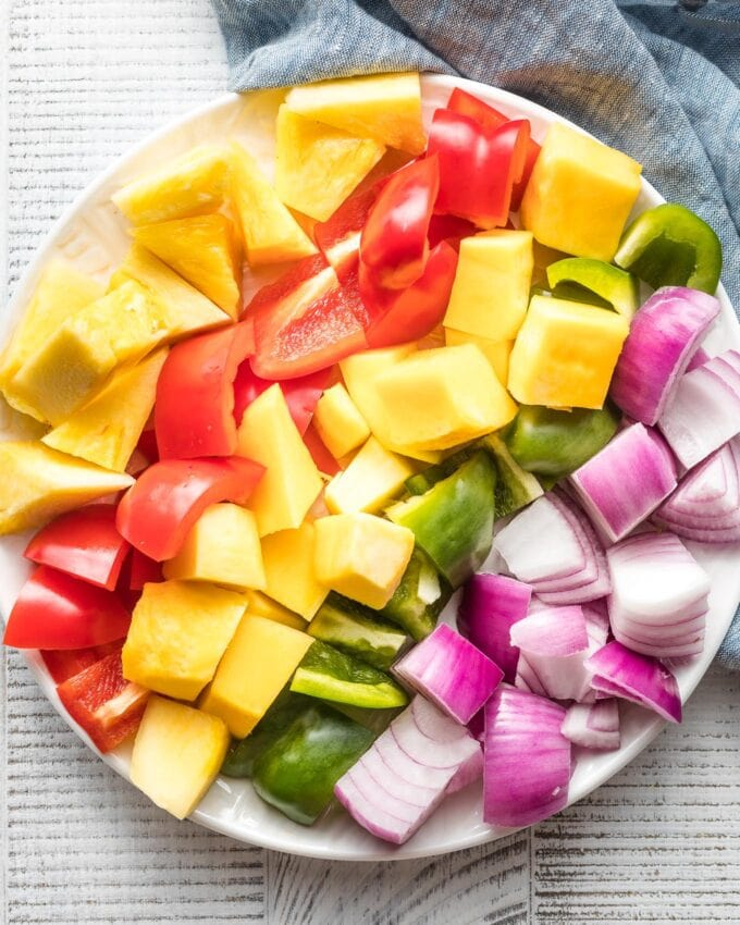 Cubed mango, red bell pepper, pineapple, green bell pepper, and red onion lined up on a plate, ready to be threaded onto kabobs.