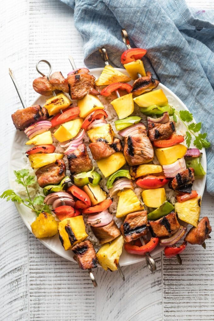 Kabobs with pork, pineapple, mango, onions, and peppers piled on a white plate.