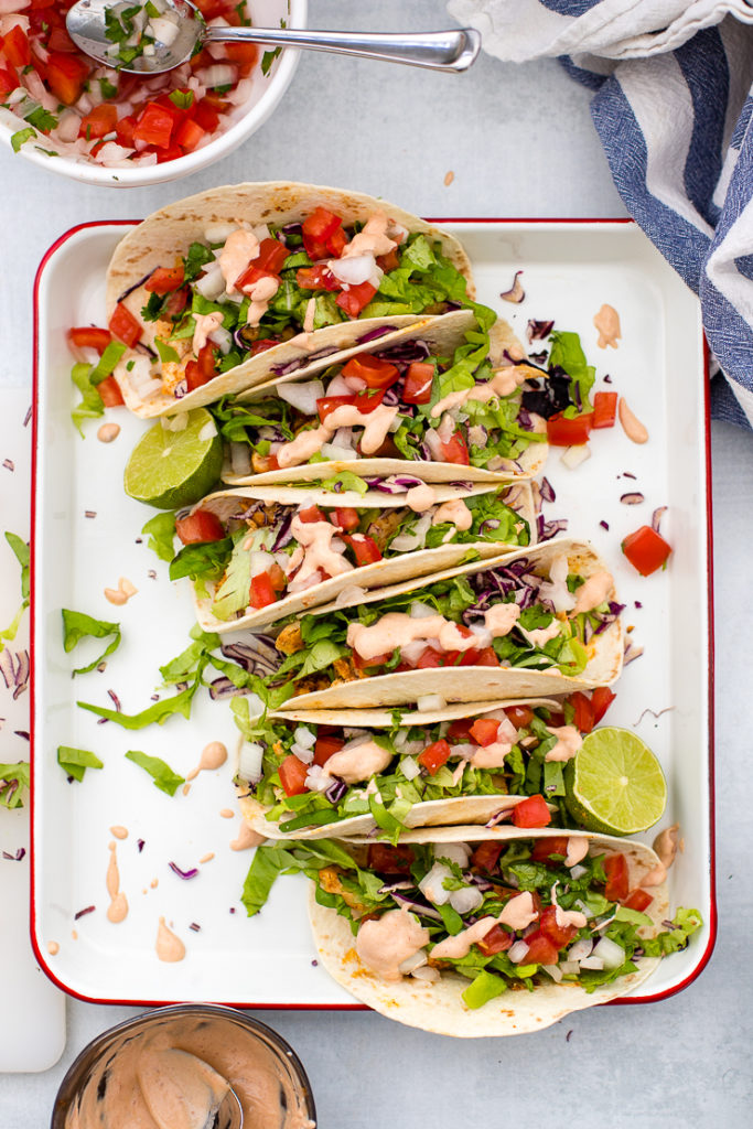 Six skinny Baja chicken tacos arranged on a bright white tray with all the fixings.