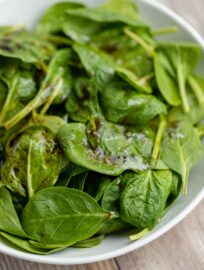 A large white bowl filled with balsamic spinach salad with sea salt.