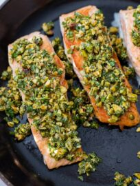 Three salmon filets topped with a pistachio herb mixture in the cast-iron pan in which they were seared.