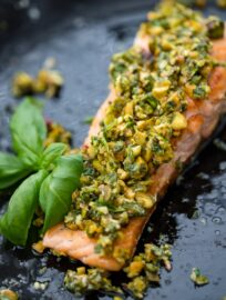 Close-up of pistachio herb salmon with a basil garnish.