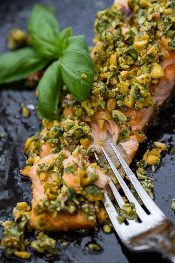 Close-up of pistachio herb salmon being flaked with a fork.