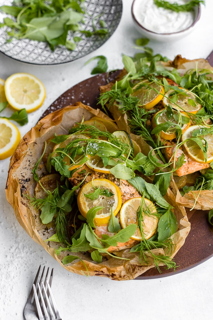 Parchment baked lemon salmon served in a packet with fresh arugula and herbs, served on a cutting board.