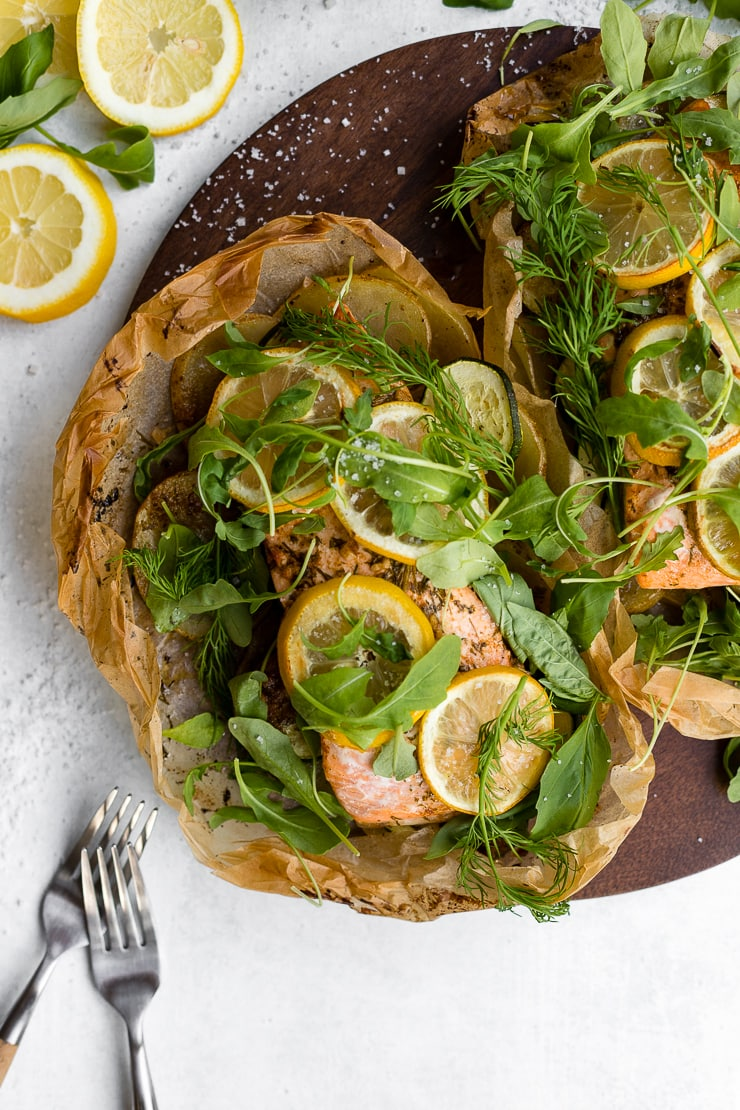 Two servings of parchment lemon salmon sprinkled with fresh dill, basil, and arugula.