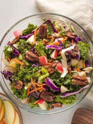 Apple cabbage slaw with shredded carrots and a brown sugar cider vinaigrette, served in a clear glass bowl.