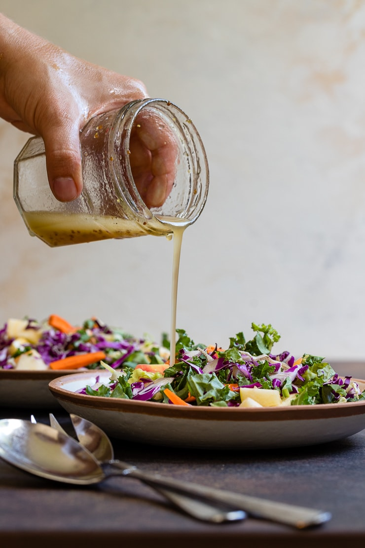 Hand pouring salad dressing out of a small jar and onto an apple cabbage salad.