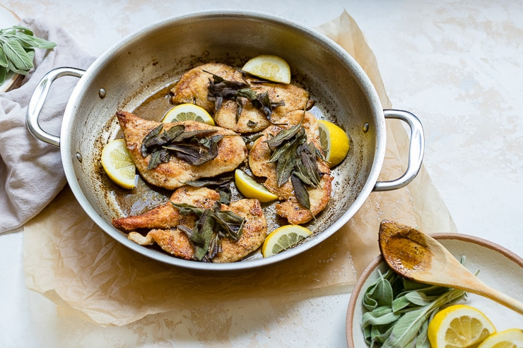 Large skillet filled with browned butter sage chicken with lemon slices.