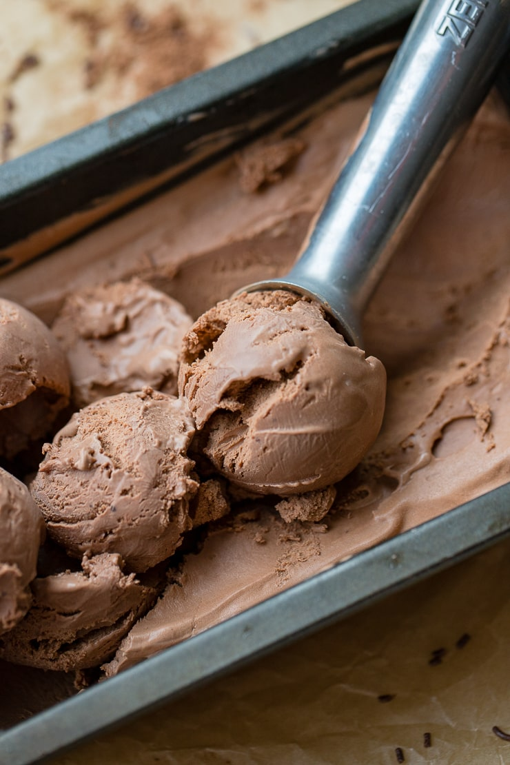 Close up of a metal ice cream scoop serving double chocolate ice cream.