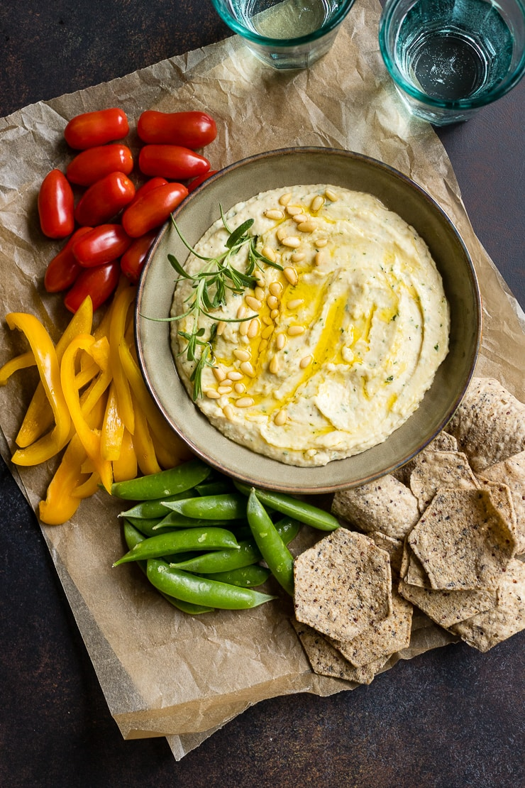 A bowl of garlic rosemary white bean dip surrounded by fresh veggies and chips.