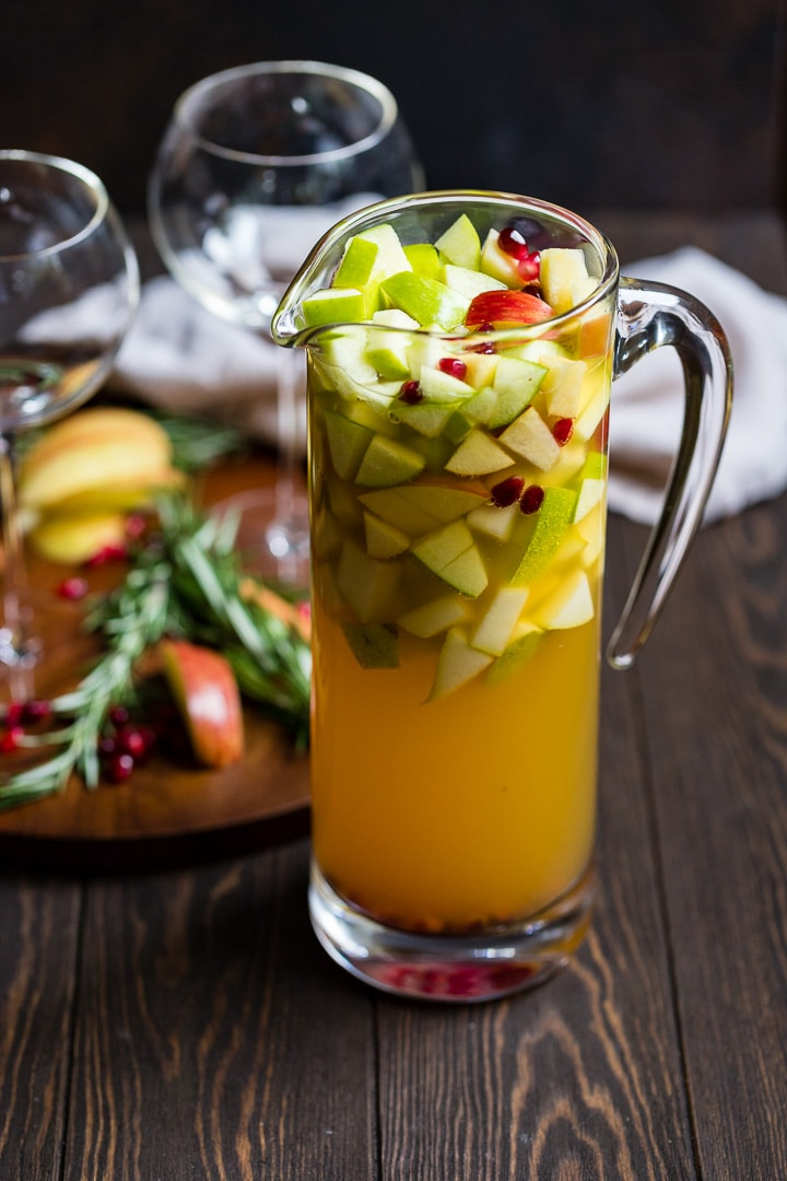 Large pitcher of autumn harvest white sangria with apples, pears, white wine, apple cider, and pomegranate seeds.