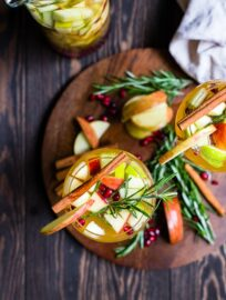 Overhead shot of two glasses filled with autumn harvest white sangria, garnished with rosemary and cinnamon sticks.
