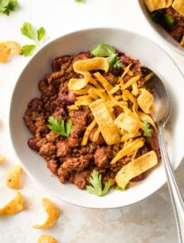 Bowl of beef and bean chili with cheese and corn chips.