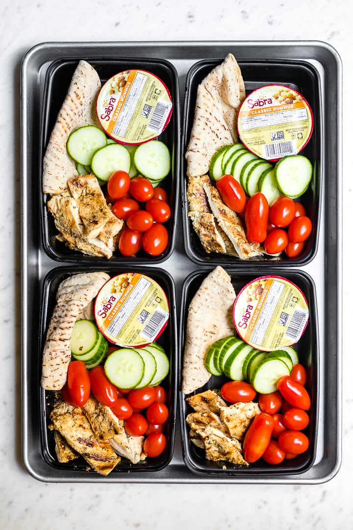 Four prepped chicken hummus bistro boxes arranged on a sheet pan.