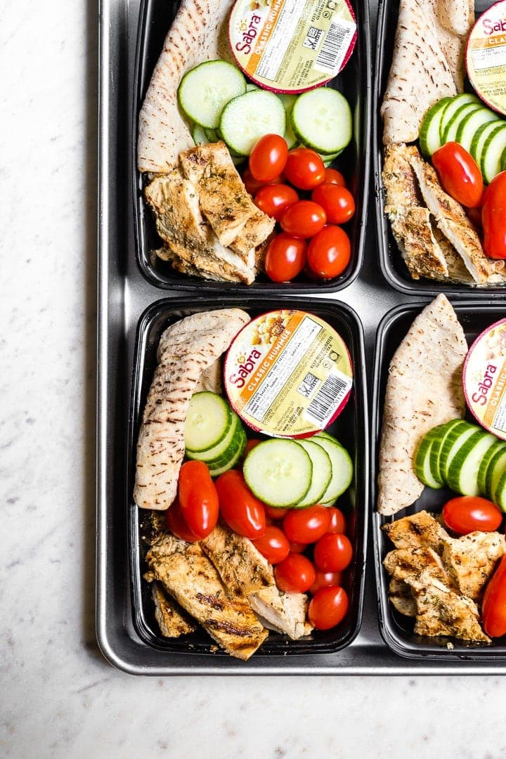 Chicken hummus bistro boxes packed with cucumber, cherry tomatoes, and a mini pita.