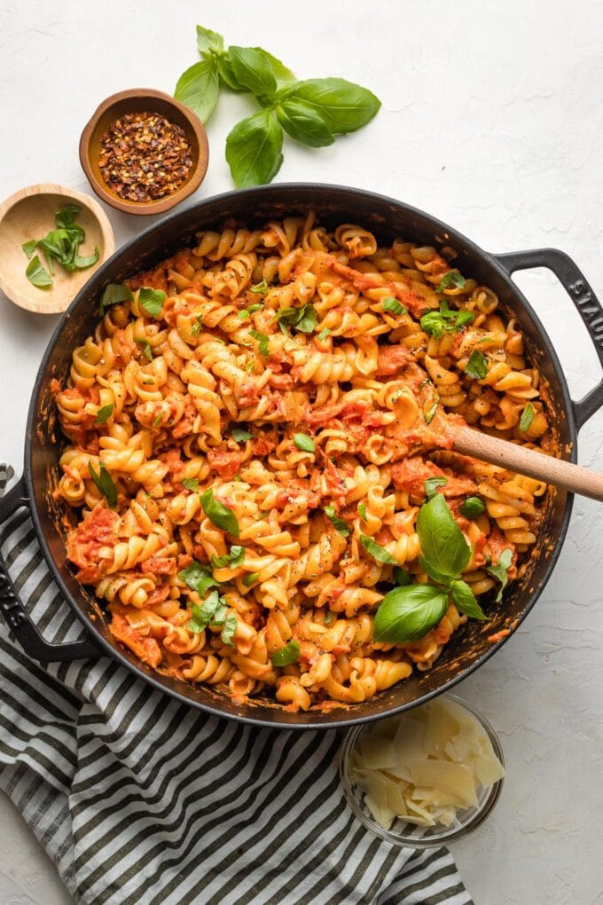 Rotini with homemade vodka sauce in a pan, garnished with basil.