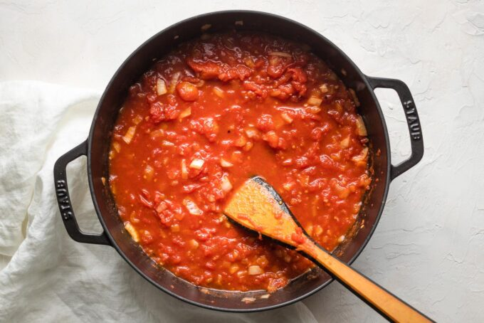Whole tomatoes crushed and added to the pan.