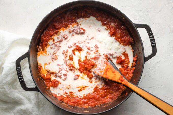 Cream just poured into a pan of tomato sauce.