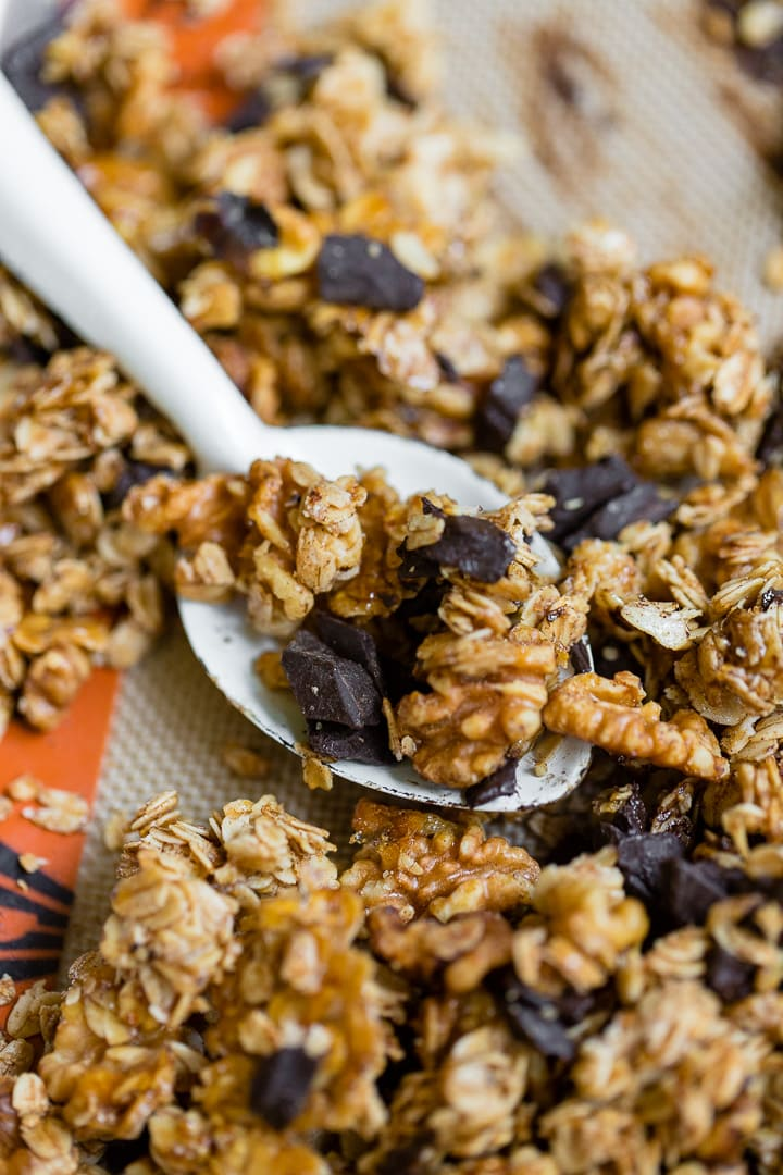 Close-up of a spoon stirring honey walnut granola just baked on a sheet pan.