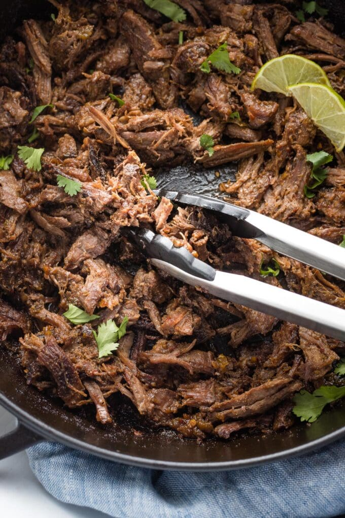 Close-up of tongs serving barbacoa out of a skillet.