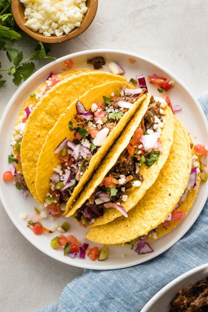 White plate with four hard shell tacos filled with homemade barbacoa beef.