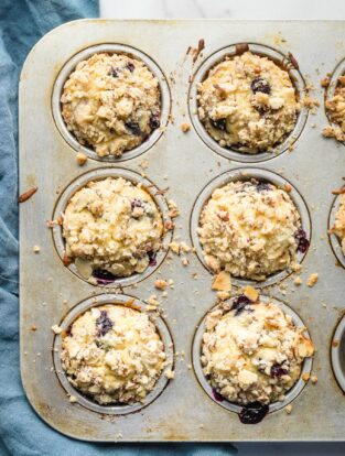 Six blueberry muffins with almond streusel topping in a baking tin.