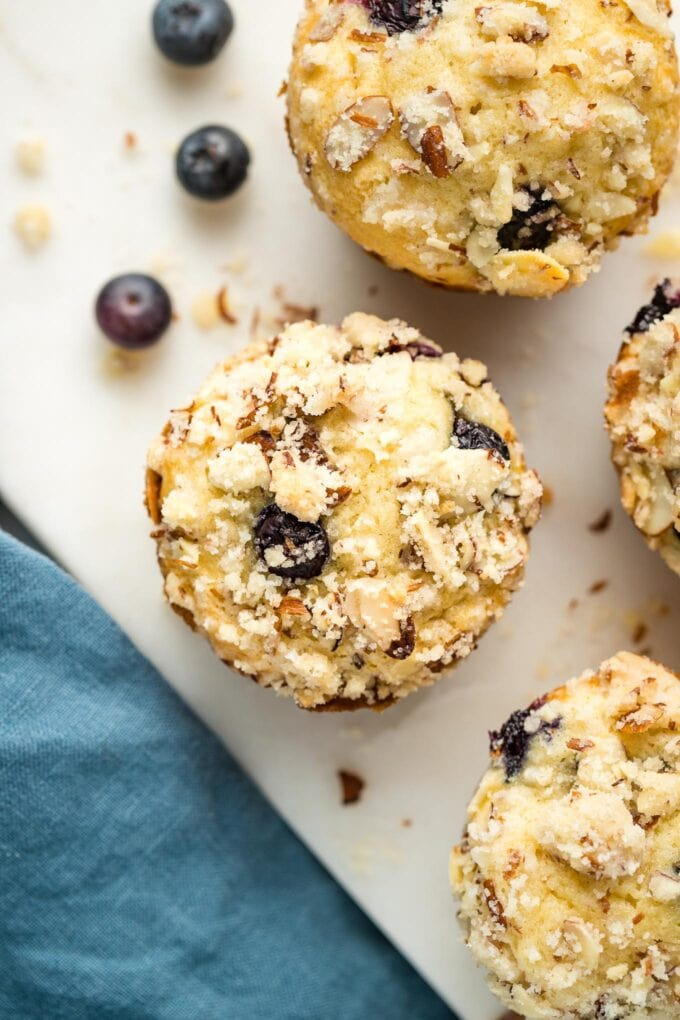 Close up of a blueberry almond muffin on a marble white board.