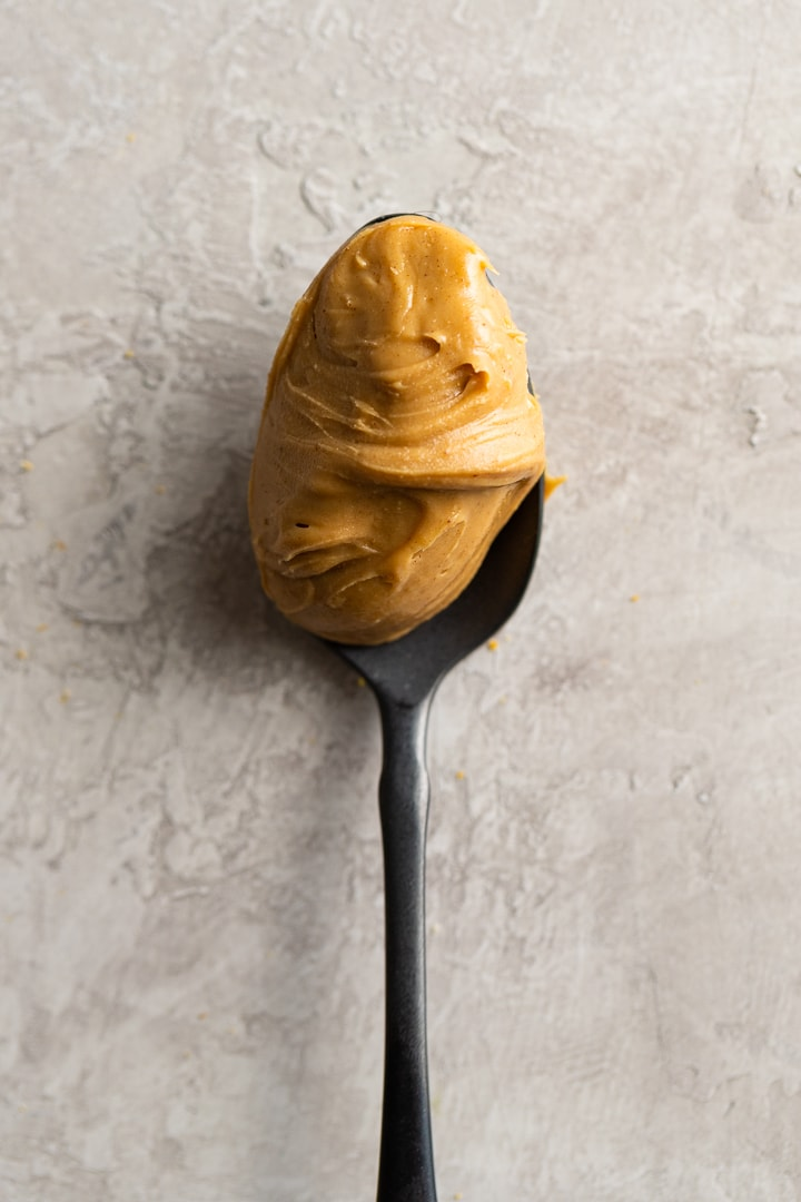 Close-up of creamy peanut butter on a black spoon.