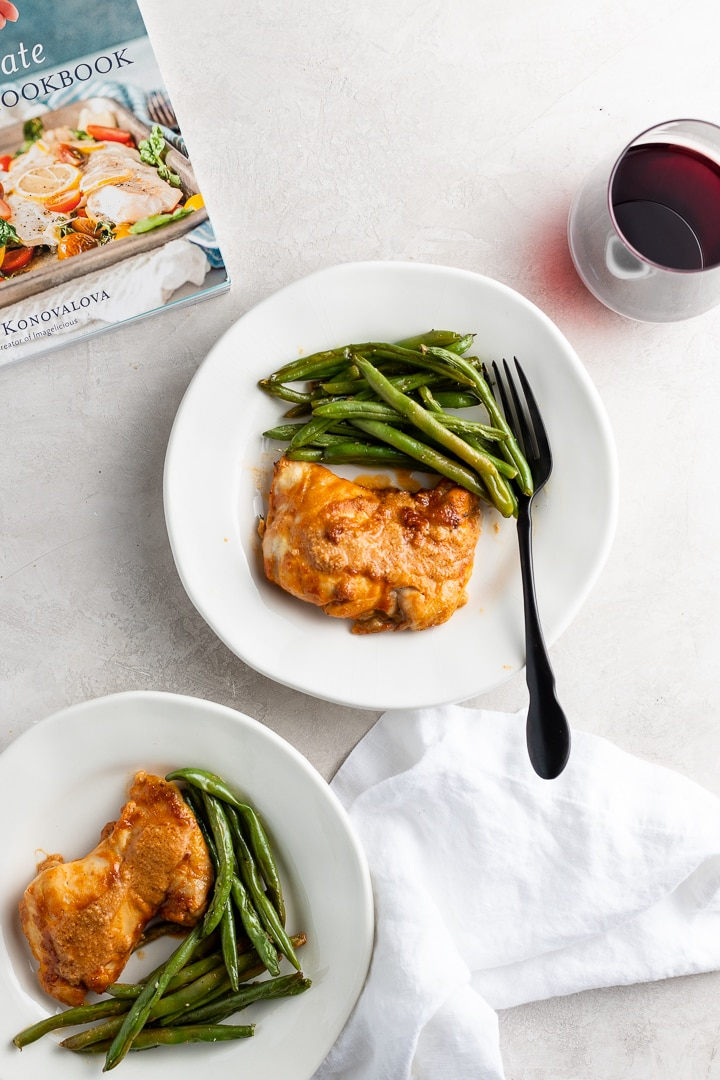 Plates of chicken thighs with peanut sauce and green beans, with a copy of The Ultimate One-Pan Oven Cookbook in the background.