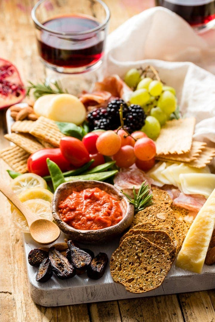 Photo of a gorgeous cheeseboard filled with cheese, crackers, meat, dip, veggies, and fruit.