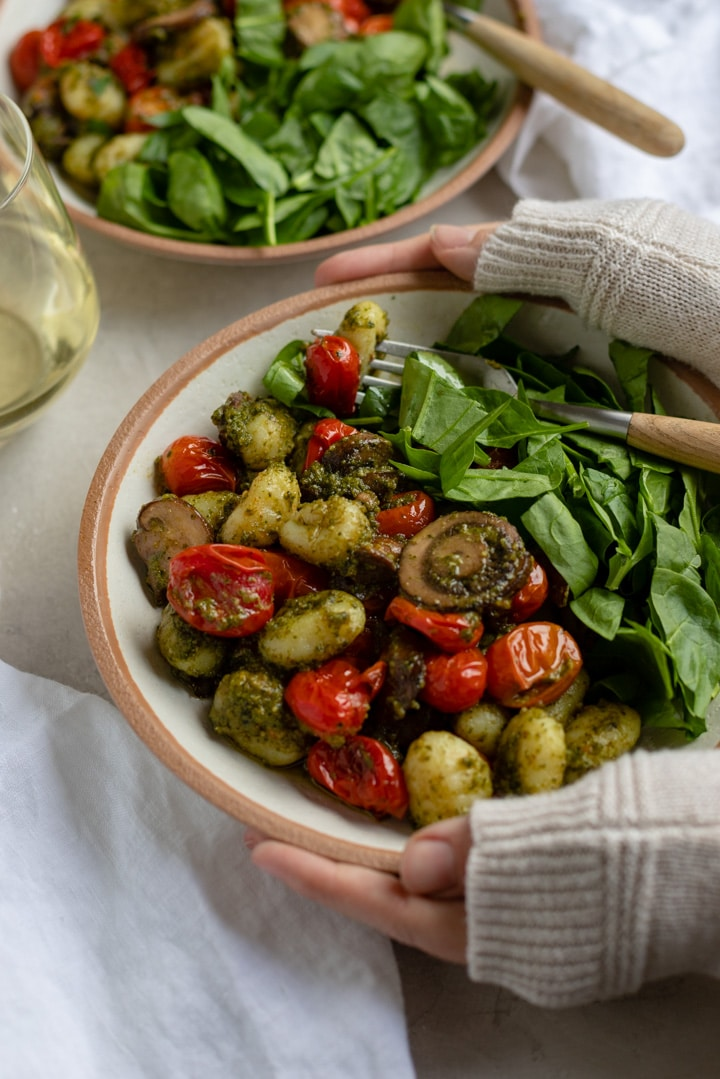 Two hands partially covered by a sweater and holding a bowl of gnocchi with pesto.