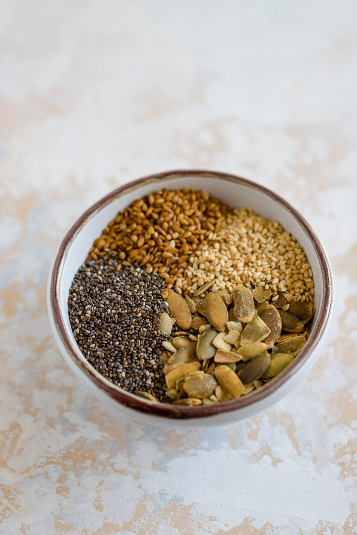 Sesame seeds, flax seeds, chia seeds, and pumpkin seeds in a small bowl.