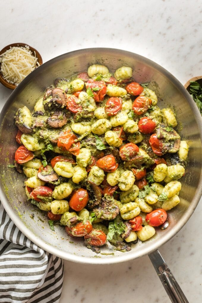 Skillet with gnocchi, pesto, mushrooms, and charred cherry tomatoes.