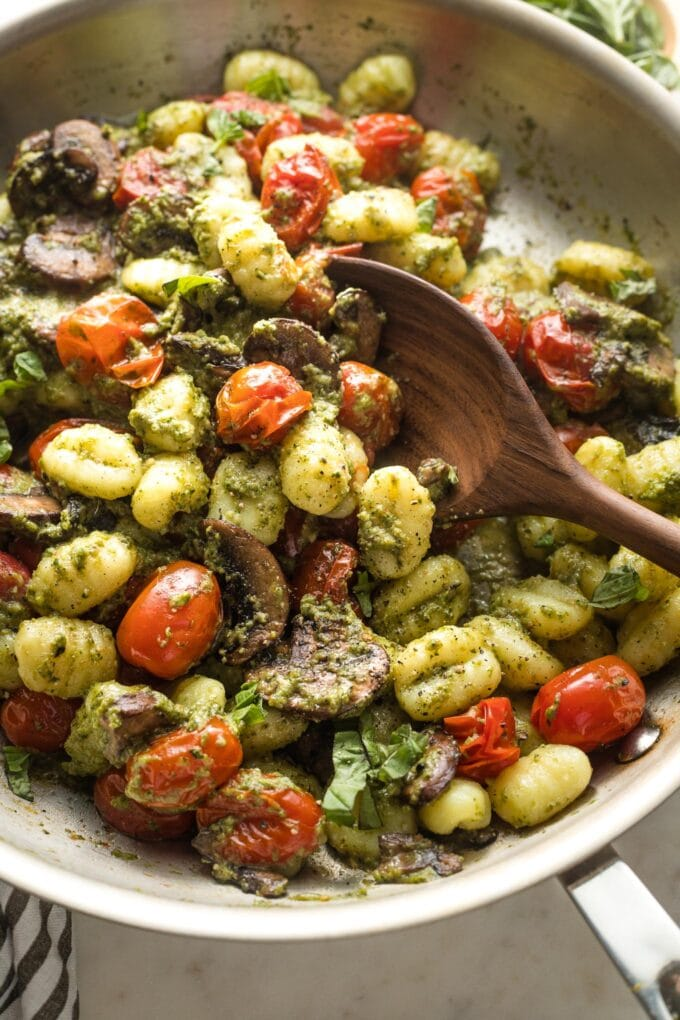 Wooden spoon stirring a large skillet full of pesto gnocchi.