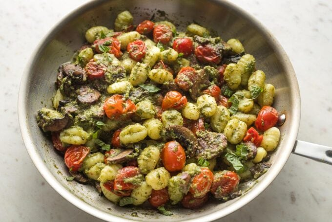 Skillet with gnocchi pesto all mixed together.