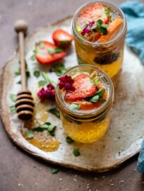 Two tequila kombucha cocktails with fresh herbs and fruit arranged on a small platter with a drizzle of honey.