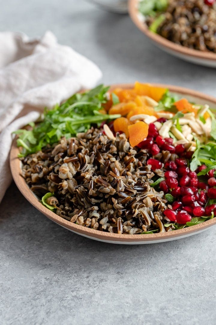 A bowl of wild rice winter salad with arugula, pomegranate arils, almonds, and dried apricots.