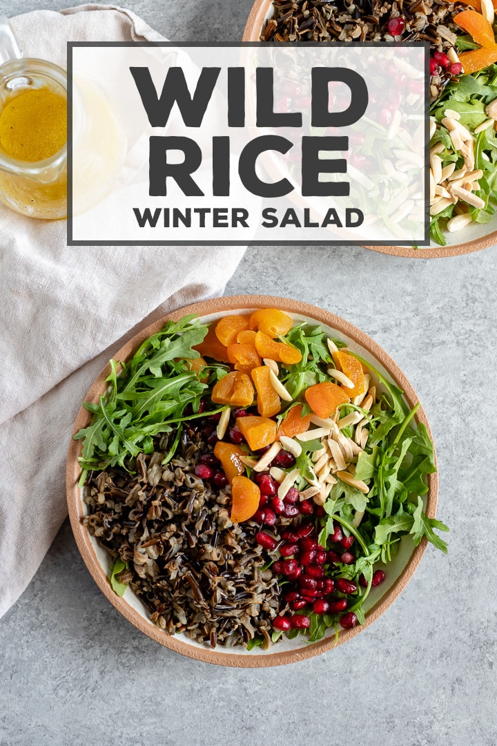The most delicious healthy salad! A hearty wild rice winter salad uses seasonal greens and pomegranates for a filling and fresh side that is easy to throw together. #wildrice #salad #healthyrecipes