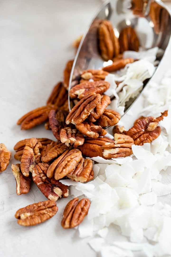 Close-up of whole pecans and unsweetened coconut flakes.
