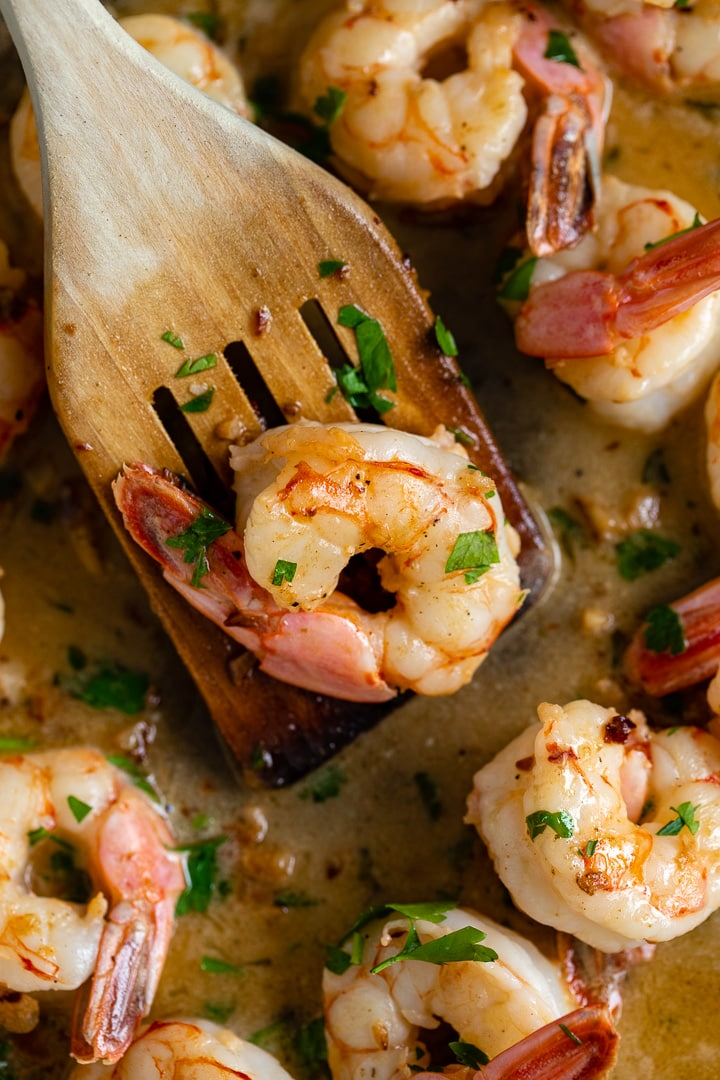 Close-up of a large shrimp cooked in garlic butter with fresh lemon juice and parsley.