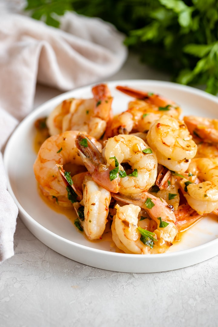A small white plate filled with garlic butter shrimp.