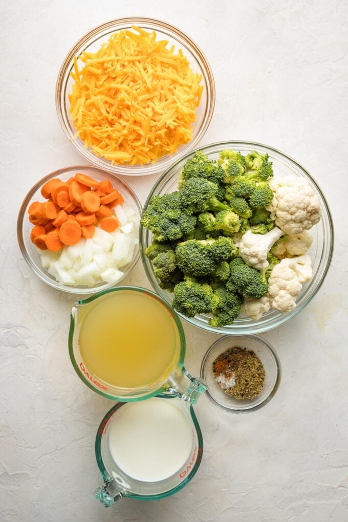 Prep bowls holding shredded cheddar cheese, carrots, onions, broccoli, cauliflower, broth, milk, and seasonings.