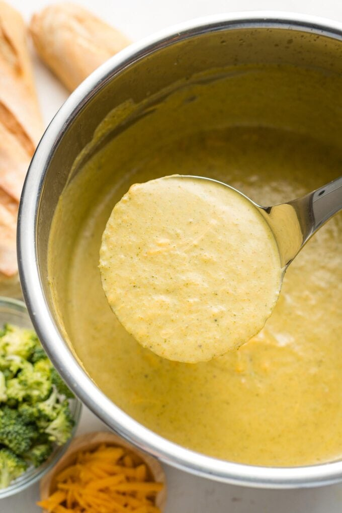 Ladle lifting broccoli cheddar soup out of an Instant Pot.