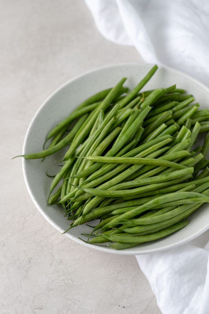 Close-up of trimmed French green beans in a white bowl.