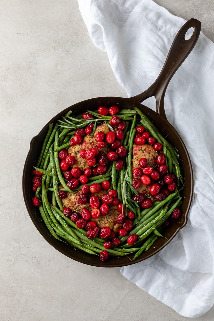 Overhead view of a Marquette Castings cast iron skillet holding balsamic cranberry chicken with green beans.