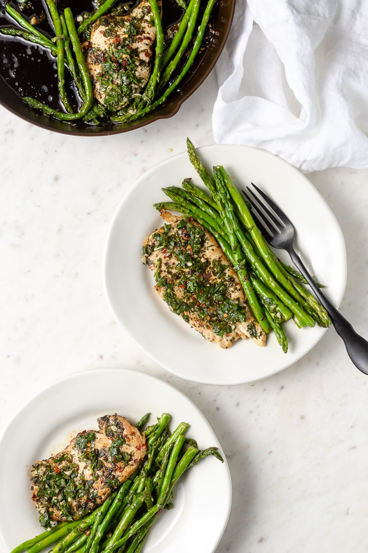 Plated dishes of chimichurri chicken with asparagus.