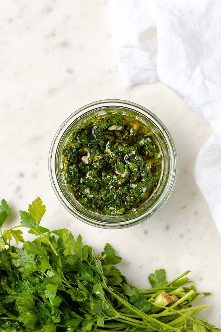 Close-up of a bowl of bright green chimichurri made by hand.