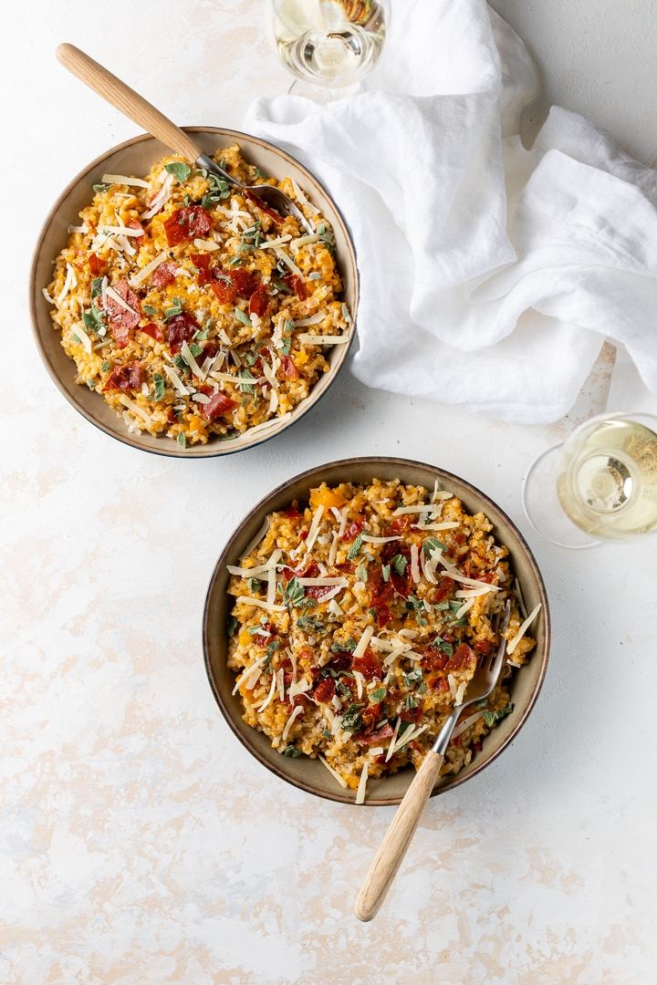 Two bowls filled with Instant Pot butternut squash risotto topped with crisped Prosciutto, fresh sage, and Parmesan, served with glasses of white wine.