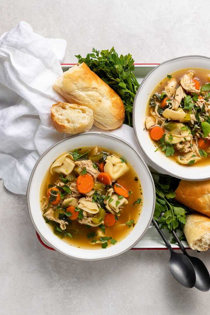 Two piping hot bowls of tortellini chicken noodle soup served with fresh crusty bread.
